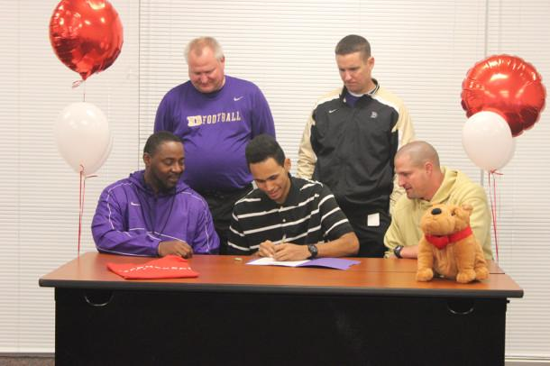 Dixon is seen signing with McPherson College