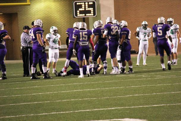 Senior Jacob Dodson is watched by his teammates as he lays motionless on the turf. Dodson left the Azle game with an injury to his left knee.
