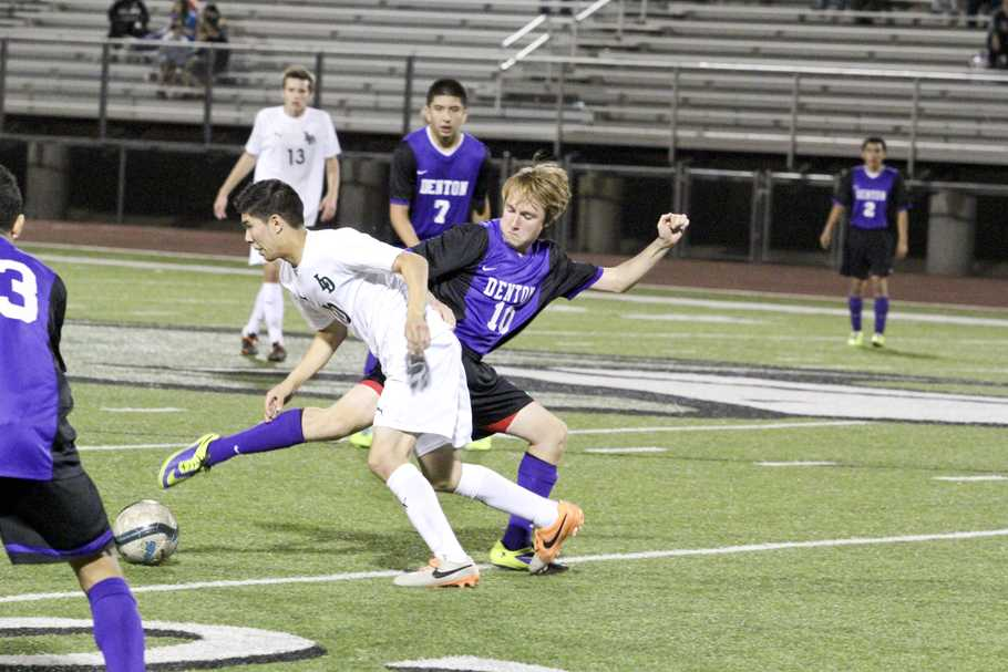 Trying to keep the ball from a defender during the Lake Dallas game is junior Zach Ardis. The Broncos won the game 2-1 to clinch the second see out of district 11-4A.