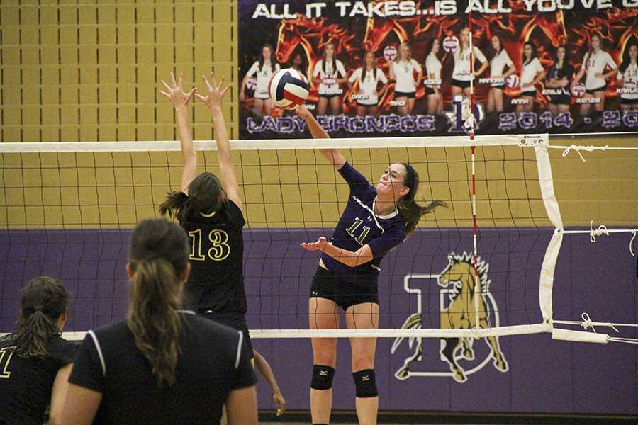 Junior Kenzie Dozer spikes the ball past a Rider player during Denton's close 3-2 win over the Raiders. The victory put the Lady Broncos in sole possession of first place.