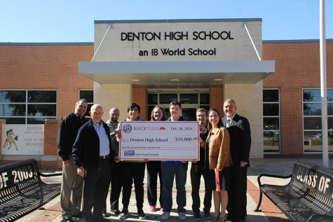 Members from Buick present a check for $10,000 to the Denton High School Administration. Denton High earned the $10,000 for participating in a test drive fundraiser with Buick.