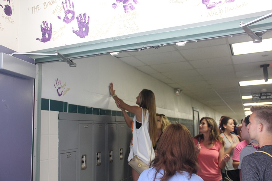 Varsity+Cheer+Captain+Lexi+Atkinson+places+her+handprint+on+the+wall+to+symbolize+her+legacy.